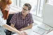 Business couple looking at each other while using laptop in creative office