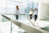Blurred motion of businesswomen walking at office hallway