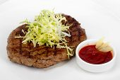 Succulent Thick Juicy Portions Of Fried Fillet Steak, Served With A Tomato Sauce On A White Plate