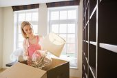 Woman removing lamp from cardboard box at new home