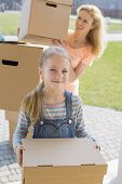 Mother and daughter with cardboard boxes moving into new house