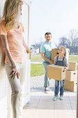 Woman looking at family with cardboard boxes entering new home