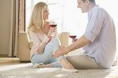 Loving couple looking at each other while drinking red wine at home