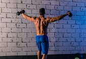 gym man rising hex dumbbells weightlifting rear view