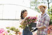Happy gardeners holding flower pot outside greenhouse
