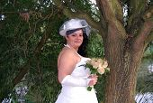 Young brunette overweight bride posing for the camera outdoors