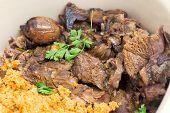 turkish roast lamb, kuzu tandir, with bulgur pilaf in a serving bowl, closeup