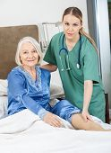 Portrait of female caretaker checking senior woman's leg in bedroom at nursing home
