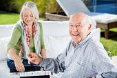 Portrait of happy senior man playing rummy with woman at nursing home