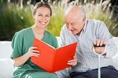 stock photo of nurse  - Portrait of happy female nurse reading book for senior man at nursing home - JPG