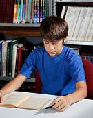 Teenage schoolboy reading book while sitting at table in library