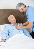 Male caretaker examining senior man with stethoscope in bedroom at nursing home