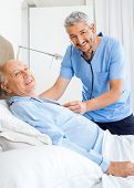 Portrait of happy male caretaker examining senior man in bedroom at nursing home