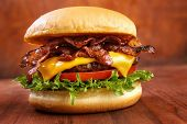 stock photo of gourmet food  - Bacon burger with beef patty on red wooden table - JPG