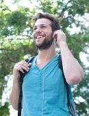 Young Man Smiling With Backpack And Earphones Outdoors