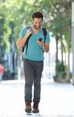 Smiling Man Walking In The City With Mobile Phone And Bag