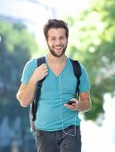Happy Young Man Walking Outdoors With Cellphone