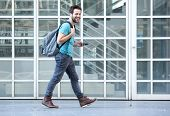 Young Man Walking On Sidewalk With Mobile Phone And Bag