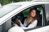Young Business Woman Driving Car And Talking On Mobile Phone