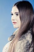 Fashionable Girl With Long Hair. Young Woman In Fur Coat On Blue.
