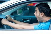 stock photo of outrageous  - Closeup portrait dumbstruck dumbfounded young sitting man in blue shirt wide open eyes and mouth by drivers in front of him isolated city street background - JPG