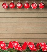Red ribbon with white stars and christmas baubles on wooden background