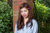 stock photo of filipina  - Pinoy woman in a green garden on farm leaning against brick pillar - JPG