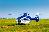 Police Helicopter On A Green Grass Field Preparing To Take Off