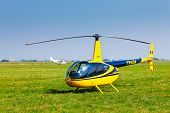 Helicopter On A Green Grass Field Preparing To Take Off