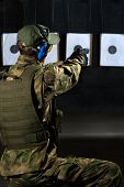 picture of shooting-range  - Man shooting with rifle at a target in shooting range - JPG