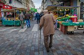 An old man walks among vegetable and fruits stands in an outdoor market