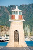 Beautiful Lighthouse On The Background Of Mountains And Moored Yachts