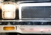 Detail Of Illuminated Headlight And Grille Of Car
