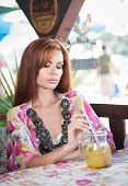 picture of woman red blouse  - Attractive red hair young woman with bright colored blouse drinking lemonade on a terrace - JPG