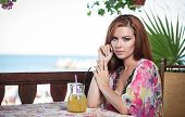 Attractive red hair young woman with bright colored blouse drinking lemonade on a terrace