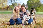 foto of shepherd dog  - A happy family of four people including mother father young child and toddler brother are sitting outside in the fallen maple leaves with their pet German Shepherd dog on an Autumn day - JPG