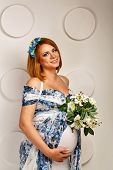 Young pregnant woman in fashionable dress