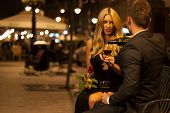 stock photo of night gown  - A couple having an elegant toast with red wine at night - JPG