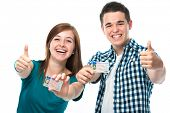 happy teens showing their driving license