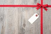 Red ribbon and bow with address label attached over wooden background