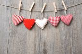 Red hearts hanging over grey wood background