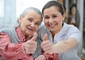stock photo of cheer-up  - Senior woman and female nurse are showing thumbs up - JPG