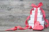 Stack of gift boxes with ribbon and bow  on old wooden background