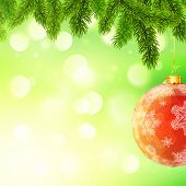 Christmas template with hanging red ball and fir tree branches on green bokeh light background