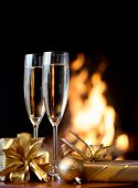 Two champagne glasses and gift boxes  in front of fireplace