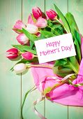 Bouquet of  tulips and card on green wooden background