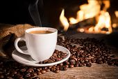 Cup of espresso coffee and coffee beans  near fireplace