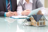stock photo of architecture  - Businessman signs contract behind home architectural model - JPG