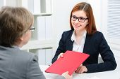 smiling woman having job interviews and receiving portfolios
