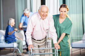 image of zimmer frame  - Portrait of happy female caretaker helping senior man in using Zimmer frame at nursing home yard - JPG